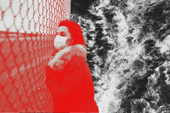 Frau mit einer Mundschutzmaske lehnt an einem Zaun